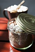 Cocoa powder with marshmallows and chocolate chips in a screw-top jar