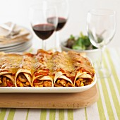 Filled tortilla rolls topped with cheese and tomato sauce and baked