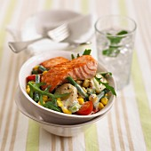 Salmon fillet on a bed of potato salad with vegetables and a mustard dressing