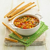 Vegetable stew with pasta and breadsticks