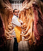 A butcher standing between hanging pig carcasses, which have been cut in half