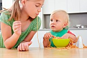A girl and a small child playing with spaghetti