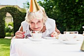 An older woman wearing a party hat sitting at a table in the garden
