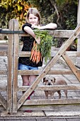 Girl standing with a bunch of carrots and a dog by a wooden gate