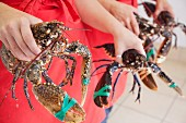 Women holding freshly caught lobsters