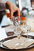A waitress pouring schnapps into a glass