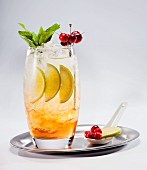Fruit cocktail with berries, limes and mint on a silver tray
