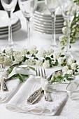 Besteck auf weisser Serviette auf einem Hochzeitstisch mit Blumendeko