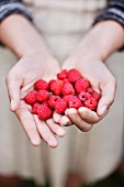 Girl with a big handful of raspberries
