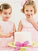 Young girls picking at a birthday cake