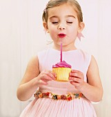 Young girl holding a birthday cupcake