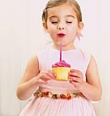 Mädchen bläst Geburtstagskerze aus