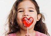 Studio shot of Hispanic girl licking heart lollipop