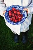 Girl holding bowl with raspebbies Image