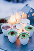 Suppe in Bechern auf winterlich dekorierten Tisch im Freien