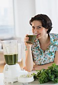 A woman drinking home-made kale juice
