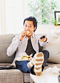 An Asian man sitting on the sofa in front of the television holding a sandwich and a remote control