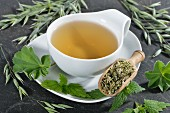 A cup of herbal tea made from oats, stinging nettle and lady's mantle