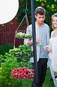 A couple at a garden party with fruit and herbs in hanging in baskets in the foreground