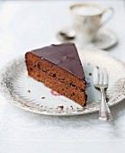 A slice of Sachertorte (rich chocolate cake from Austria) served with coffee