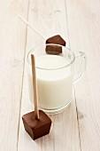 Heiße Milch und Schokoladenwürfel zum Eintauchen