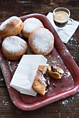 Doughnuts with icing sugar and a pain au chocolat, served with coffee