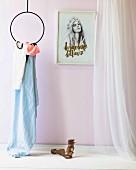 Damensandalen auf weisser Ablage neben kreisförmigem Metallgestell mit Tuch, von der Decke abgehängt, an rosa Wand gerahmtes Frauenportrait, seitlich luftiger Vorhang