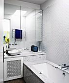 Spiegelschrank über Waschbecken neben Badewanne