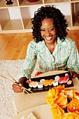 A dark-skinned woman eating sushi
