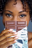 African woman holding chocolate bar in front of face