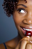 Close up of African woman eating cherry