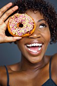 African woman holding doughnut over eye