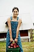 Mädchen in Latzhose trägt Eimer mit frischen Äpfeln