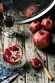 Granatäpfel, ganz und angeschnitten, mit Rotweinglas auf Holztisch