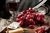 Bunch of red grapes with cheese and a vintage glass of red wine