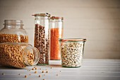 Assorted jars of beans and grains on wooden surface including corn, lentils, pinto beans, canellini beans, and peas