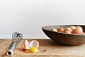 Frische Bauerneier in Holzschüssel, aufgeschlagenes Ei und Schneebesen