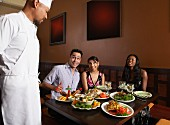 Multi-ethnic friends complimenting chef
