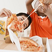 Boys eating pizza together