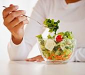 Mixed race woman eating salad