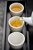 Green tea being poured from teapot into cups on tray