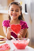 Hispanic girl holding heart-shaped cookie