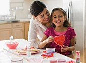 Mother and daughter making Valentine s cookies