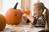 Caucasian girl carving pumpkin