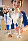 Mixed race woman pouring Champagne into glasses