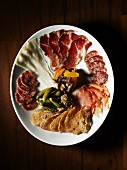 A platter of antipasti with ham, salami and pickles