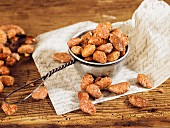 Roasted almonds in a small sieve on a wooden surface