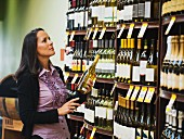 A woman standing in front of shelves of wine, choosing a bottle of wine