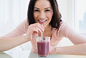 A woman drinking a smoothie through a straw