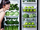 Frau vor Kühlschrank mit grünem Gemüse